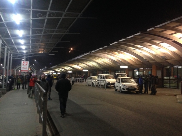 Outside the Tribhuvan International Airport. To the right, taxis. To the left, drivers. Missing: my driver.