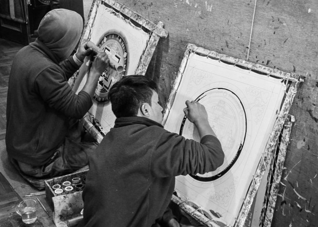 men painting mandalas